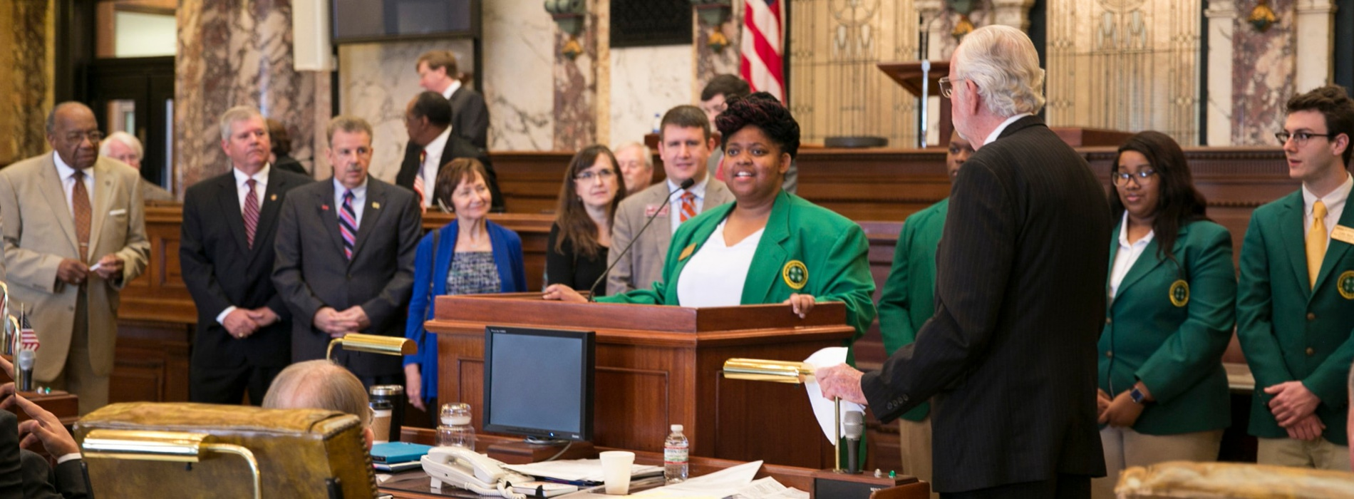 A 4-H youth addresses a congregation surrounded by her peers.