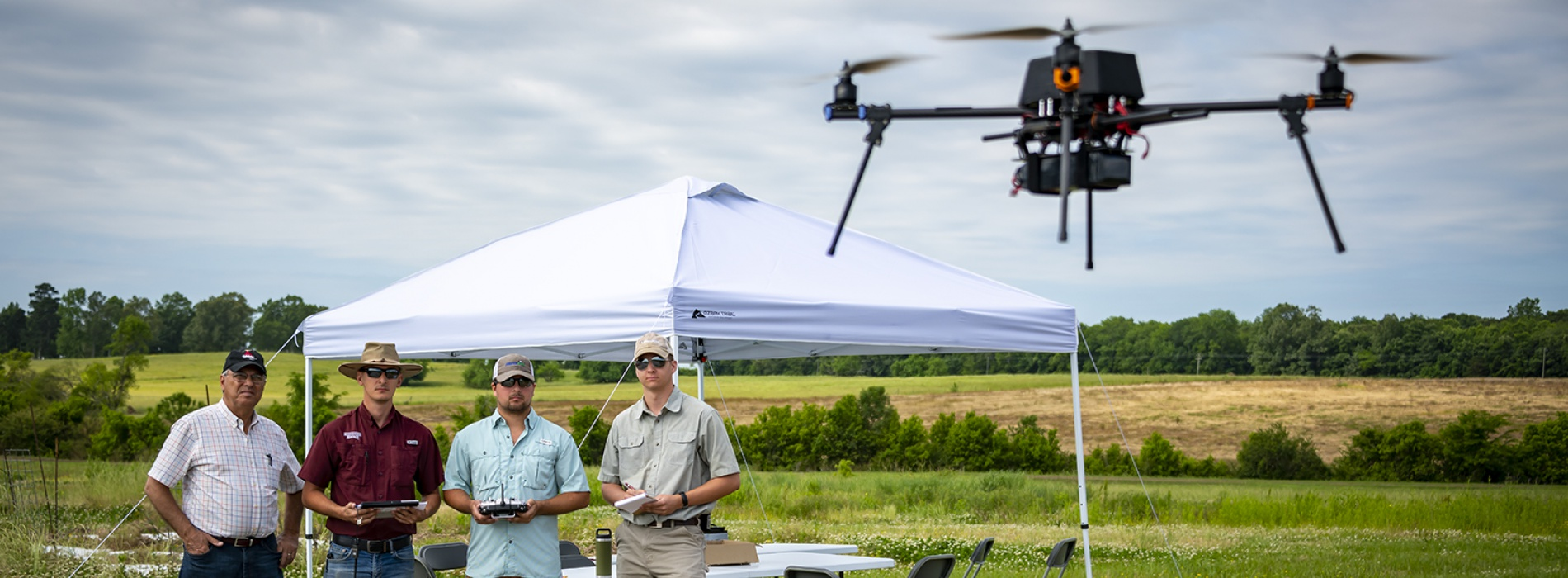 Four men stand in a field with a drone flying.